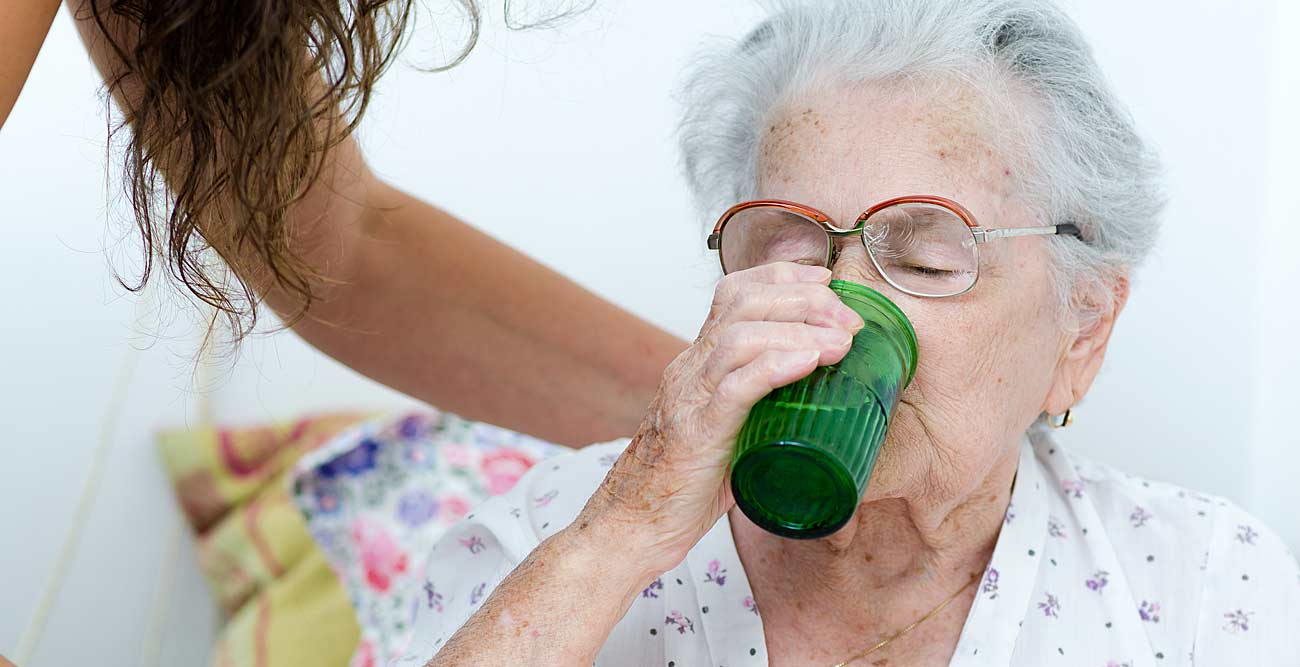 aide helping patient drink
