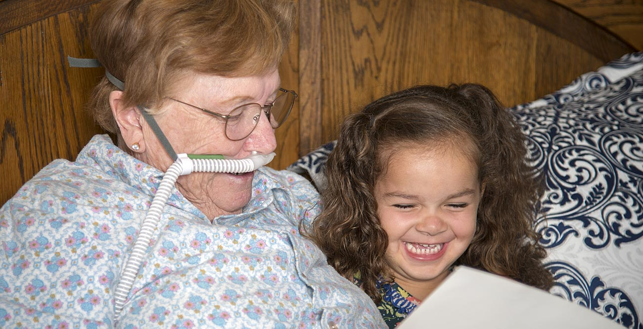 grandmother in hospice reading to child